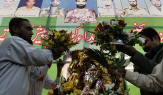 People place flower bouquets at a huge board depicting Pakistan army soldiers who were killed in NATO airstrikes on Nov. 26, during a ceremony to pay tribute to soldiers in Lahore, Pakistan, Saturday, Dec. 3, 2011. (AP Photo/K.M. Chaudary)