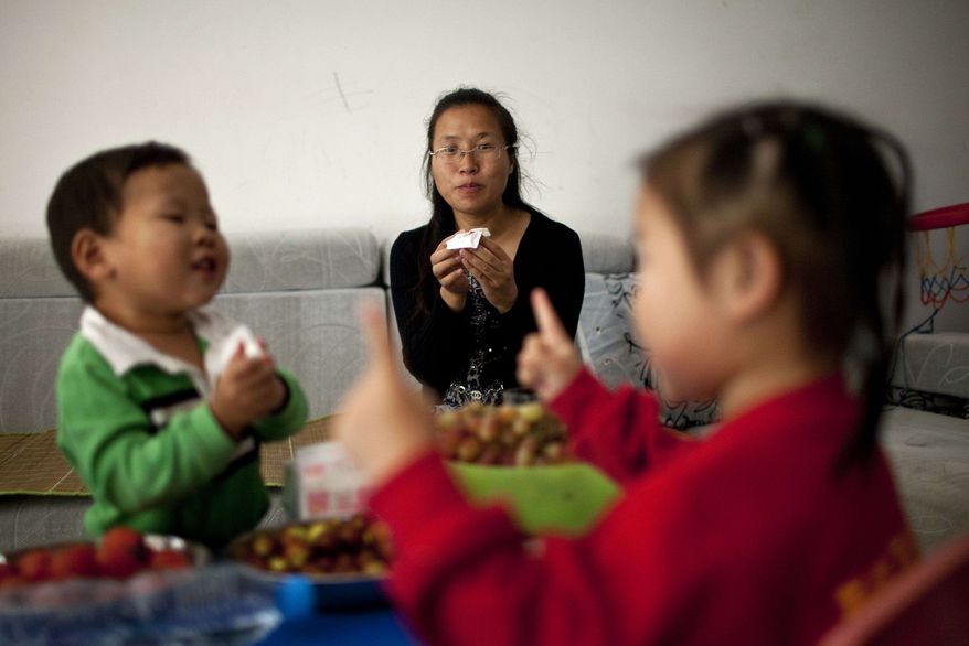 In this Monday, Oct. 17, 2011, photo, Wu Weiping, 35, watches her daughter Wang Yile, 4, right, and her son Wu Yixiao, 2, play at home in Zhuji, in eastern China's Zhejiang province. (AP Photo/Alexander F. Yuan)