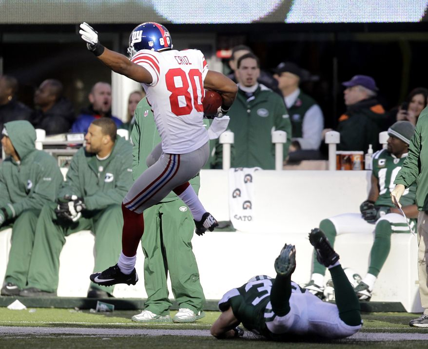 New York Giants' Victor Cruz jumps over a New York Jets defender while scoring a 99-yard touchdown during the second quarter Saturday, Dec. 24, 2011, in East Rutherford, N.J. (AP Photo/Julio Cortez)