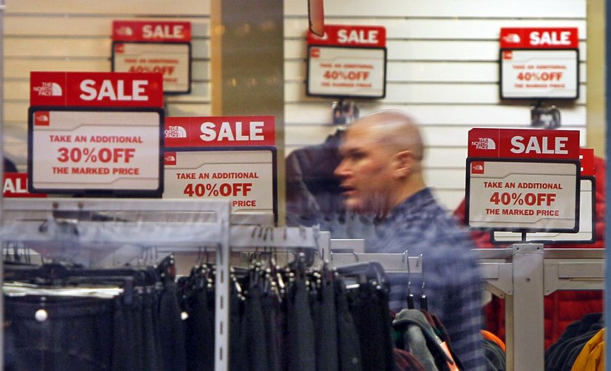 ** FILE ** Sale signs are displayed at a North Face store in Freeport, Maine, where a shopper browses the racks on Friday, Dec. 23, 2011. (AP Photo/Robert F. Bukaty, File)