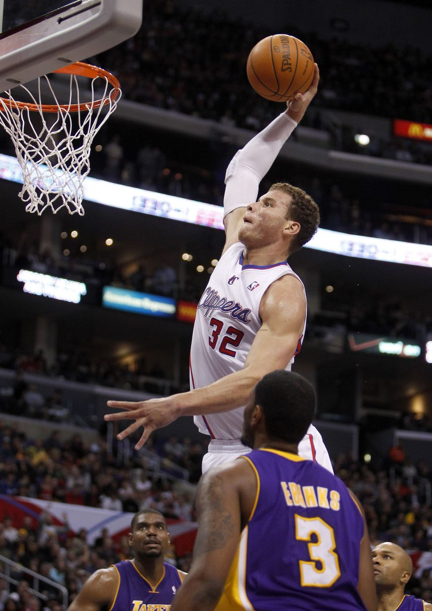 Los Angeles Clippers forward Blake Griffin (32) dunks the ball as Los Angeles Lakers' Andrew Bynum, lower left, Devin Eubanks (3) and Derek Fisher, back right, watch during the first half in Los Angeles, Wednesday, Dec. 21, 2011. (AP Photo/Alex Gallardo)