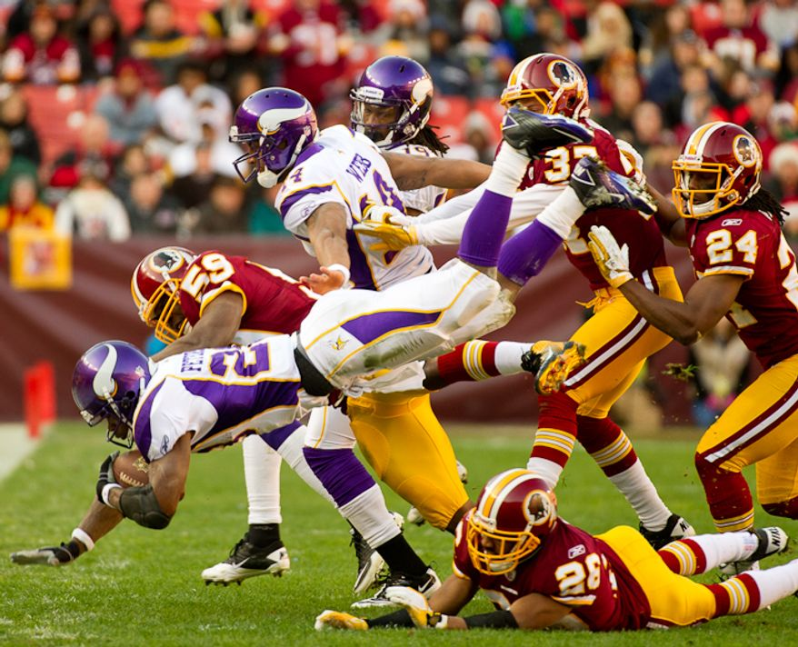 Minnesota Vikings running back Adrian Peterson (28) is stopped by Washington Redskins inside linebacker London Fletcher (59) on a run in the first quarter as the Washington Redskins take on the Minnesota Vikings at Fedex Field, Landover, MD, Saturday, December 24, 2011. (Andrew Harnik / The Washington Times)