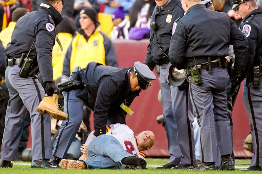 A fan is arrested for running onto the field late in the fourth quarter as the Washington Redskins lose to the Minnesota Vikings 33-26 at Fedex Field, Landover, MD, Saturday, December 24, 2011. (Andrew Harnik / The Washington Times)