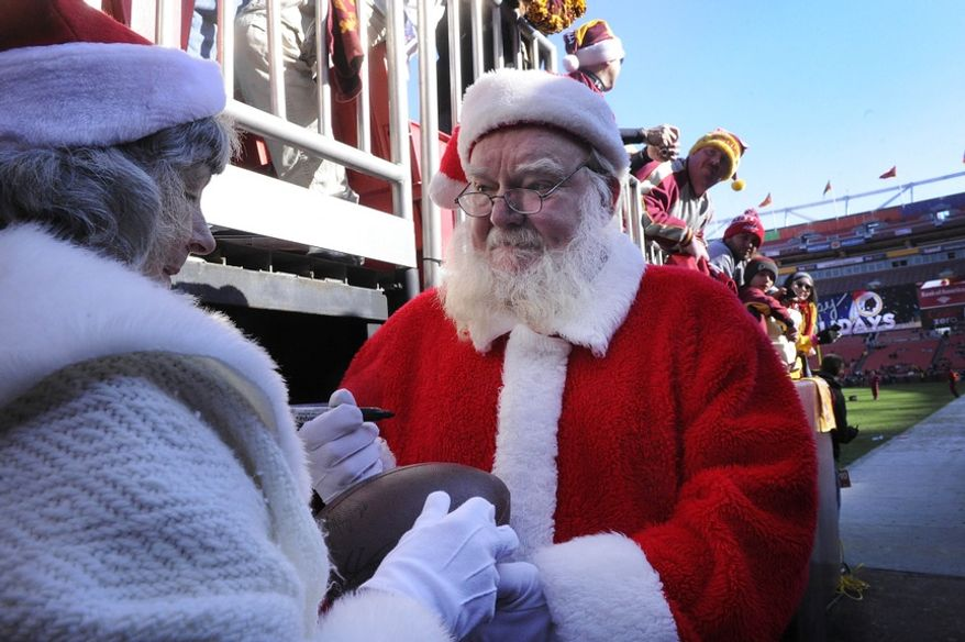 Santa and Mrs. Claus sign Redskins memorabilia before the game at FedEx Field in Landover, Md., on Saturday, Dec. 24, 2011. (Preston Keres/Special to The Washington Times)