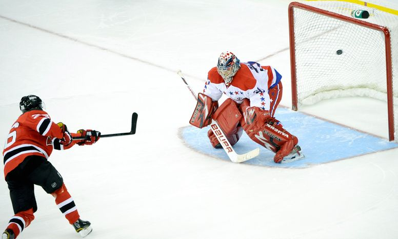 New Jersey Devils' Patrik Elias, left, of the Czech Republic, scores past Washington Capitals goaltender Michal Neuvirth during a shootout of an NHL hockey game Friday, Dec. 23, 2011, in Newark, N.J. The Devils won 4-3 in a shootout. The Caps are 6-9-1 away from home and have struggled because they've started slowly. (AP Photo/Bill Kostroun)