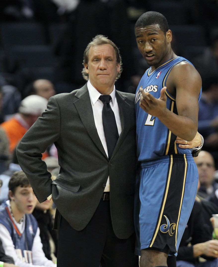 Washington Wizards coach Flip Saunders listens to Washington Wizards' John Wall (2) talks about the offense in the first half of an NBA basketball game against the Charlotte Bobcats in Charlotte, N.C., Saturday, Jan. 8, 2011. (AP Photo/Bob Leverone)