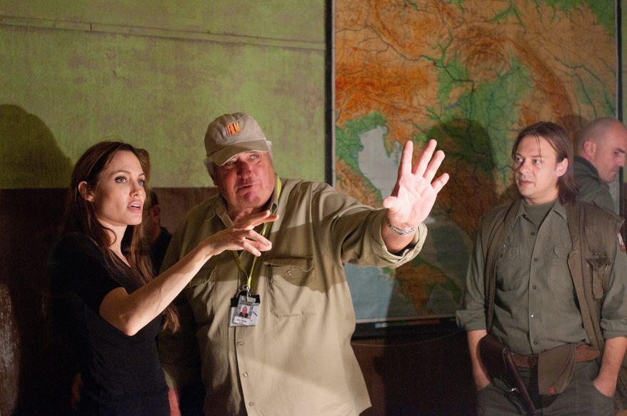 "Writer-director Angelina Jolie works with the director of photography Dean Semler (center) during the filming of ""In the Land of Blood and Honey."" The film was a balancing act as Ms. Jolie sought to tell a story representing all sides in the Bosnian conflict. (Film District via the Associated Press)"