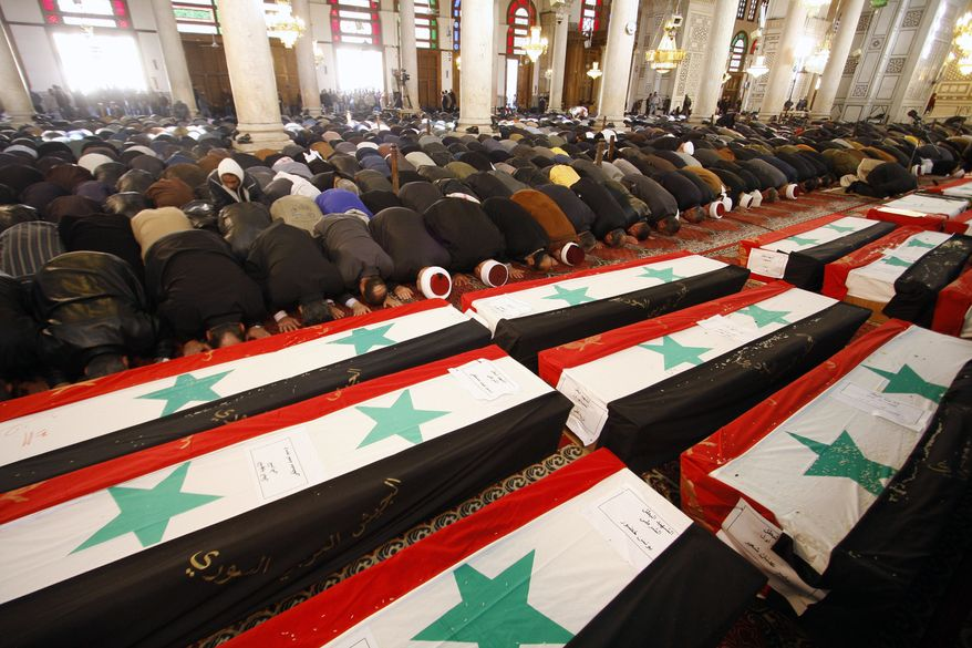 Mourners pray at a mass funeral on Saturday, Dec. 24, 2011, for 44 people killed in twin suicide bombings that targeted intelligence agency compounds in Damascus, Syria, the day before. (AP Photo/Muzaffar Salman)