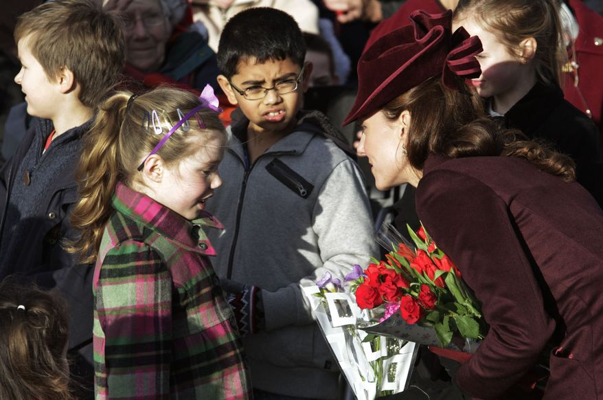 The Duchess of Cambridge (right), nee Kate Middleton, receives flowers from children after she and other members of the royal family attended Christmas services at St. Mary Magdelene Church on the grounds of Sandringham, Queen Elizabeth II's Norfolk retreat, in northeast England on Sunday, Dec. 25, 2011. (AP Photo/Lefteris Pitarakis)