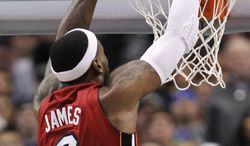 Miami Heat forward LeBron James dunks during the first half against the Dallas Mavericks in Dallas, Sunday, Dec. 25, 2011. The Heat won 105-94. (AP Photo/LM Otero)