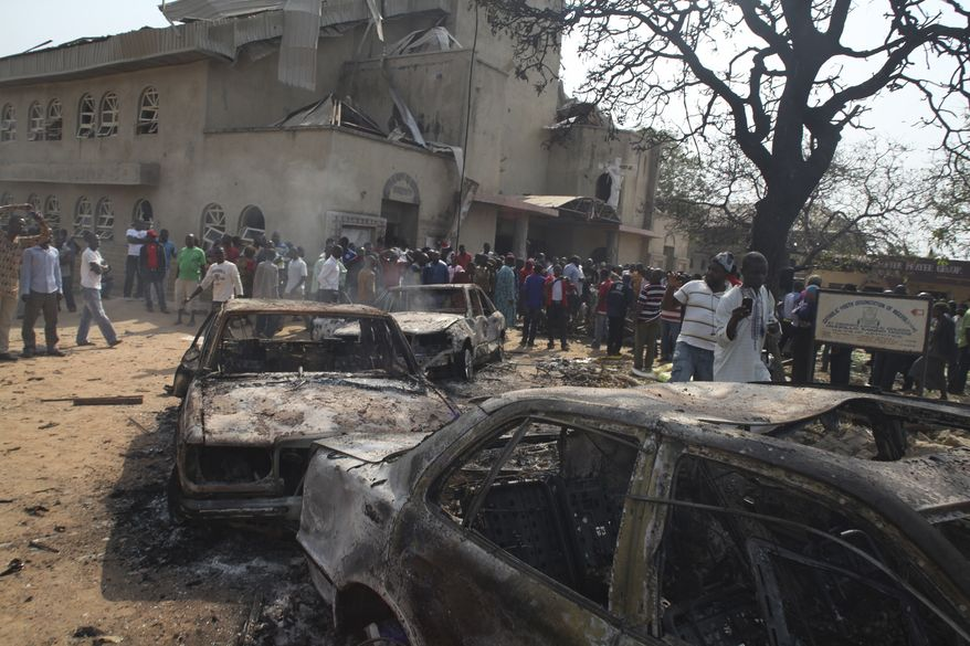 Onlookers gather around a destroyed car at the site of a bomb blast at St. Theresa Catholic Church in Madalla, Nigeria, on Sunday, Dec. 25, 2011. (AP Photo/Sunday Aghaeze)
