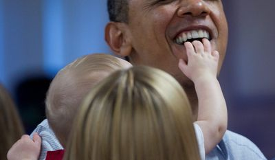 President Obama gets a mouthful of fingers from Cooper Wall Wagner, 8 months, as he poses for a photo with the infant and his parents, Greg and Meredith Wagner, during a visit to Marine Corps Base Hawaii on Sunday in Kaneohe, Hawaii. (Associated Press)
