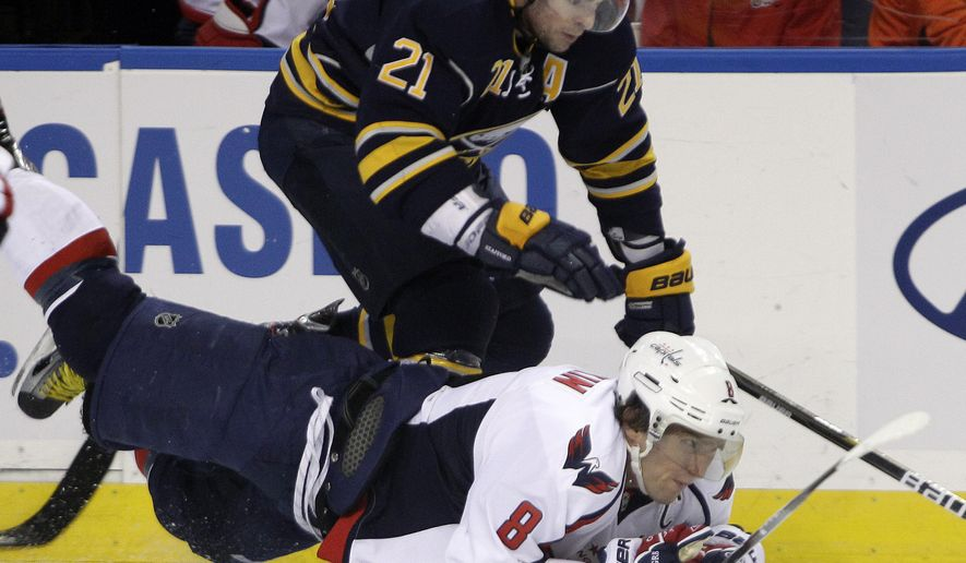 Buffalo Sabres' Drew Stafford (21) scrambles for the puck with Washington Capitals' Alex Ovechkin (8) during the first period of an NHL game in Buffalo, N.Y., Monday, Dec. 26, 2011. (AP Photo/David Duprey)