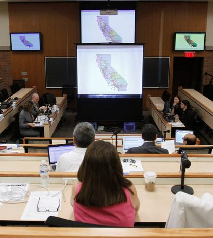 Members of the California Citizens Redistricting Commission study a district map under consideration during a hearing held in Sacramento in July. The commission produced a vastly different congressional map from what state lawmakers drew up in 2001, which essentially preserved nearly every incumbent district and deleted just one Republican district. (Associated Press)