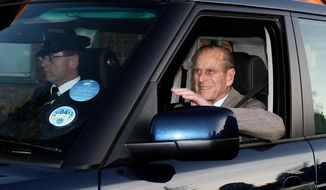 Britain's Prince Philip smiles and waves as he leaves Papworth Hospital in Cambridge, England, on Tuesday, Dec. 27, 2011, after treatment for a blocked coronary artery. (AP Photo/Press Association, Chris Radburn)