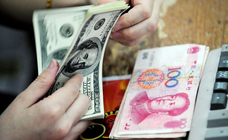 A Chinese clerk counts U.S. dollars in exchange for Chinese renminbi at a Hefei, China, bank. (