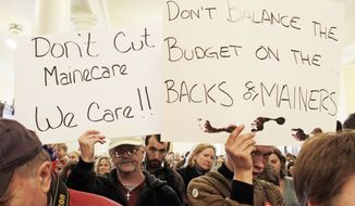 **FILE** Dozens voice their concerns about proposed budget cuts in the Medicaid system during a rally at the State House in Augusta, Maine, on Dec. 14, 2011. (Associated Press)