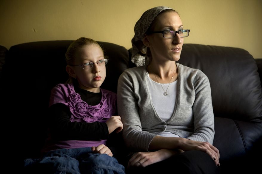 Naama Margolese, 8, sits with her mother, Hadassa, in their home in the central Israeli town of Beit Shemesh on Monday, Dec. 26, 2011. (AP Photo/Oded Balilty)