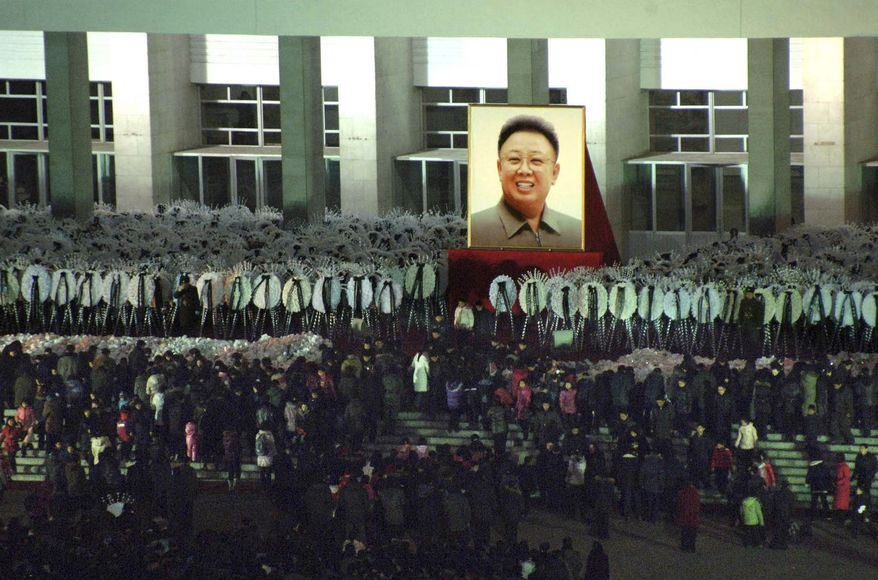 In this Tuesday, Dec. 27, 2011 photo released by the Korean Central News Agency and distributed in Tokyo by the Korea News Service, North Koreans gather in front of a huge portrait of their late leader Kim Jong-il to mourn his death in Pyongyang, North Korea. (AP Photo/Korean Central News Agency via Korea News Service)