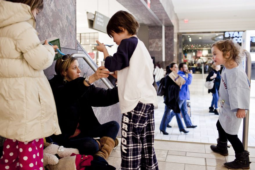 "Meredith Wade, second from left, of Bethesda, Md., shares ice cream with her children, Olivia, 7, form left, Caleb, 5, and Juliet, 3, after seeing a movie at the Tysons Corner Center mall in McLean, Va. on Dec. 26, 2011. ""Before I had kids, I would brave any crowd for a sale,"" said Meredith, ""but now I won't go in to a store."" (T.J. Kirkpatrick/ The Washington Times)"