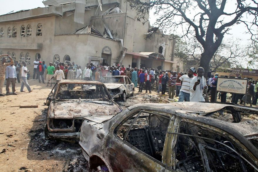 Onlookers gather around the site of a bomb blast at St. Theresa Catholic Church in Madalla, Nigeria, on Christmas Day in 2011. A radical Muslim sect, Boko Haram, claimed responsibility for the attack and for another bombing near a church in Jos, Nigeria. (Associated Press)