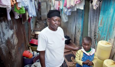 Rosalia Adhiambo, 52, and grandniece Emily, 5, both of whom are HIV positive and who share one meal a day that Mrs. Adhiambo, a widow, gets for free from a medical clinic, stand outside their shack in the Mathare slum of Nairobi, Kenya. (Associated Press)
