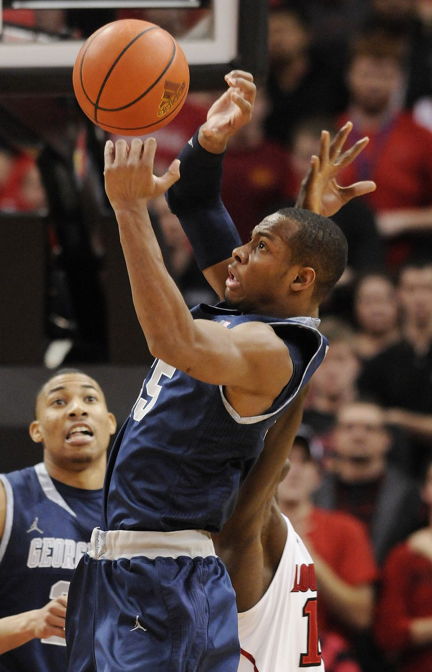 Georgetown's Markel Starks, front, grabs a rebound away from Louisville's Gorgui Dieng during the second half of an NCAA basketball game Wednesday, Dec. 28, 2011, in Louisville, Ky. Georgetown beat Louisville 71-68. (AP Photo/Timothy D. Easley)