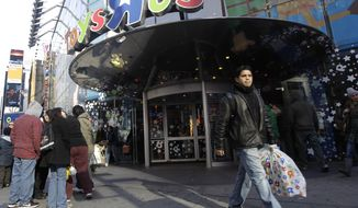"A last-minute shopper leaves the flagship store of toy retailer Toys ""R"" Us in New York's Times Square on Saturday, Dec. 24, 2011. (AP Photo/Mary Altaffer, File)"