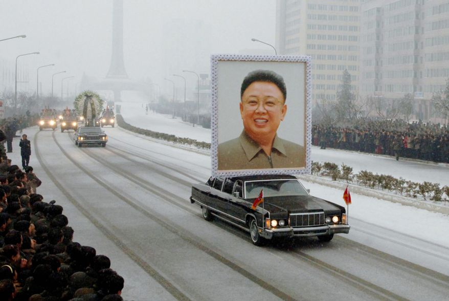 A portrait of late North Korean leader Kim Jong Il is carried past mourners during his funeral procession.  (AP Photo/Kyodo News)