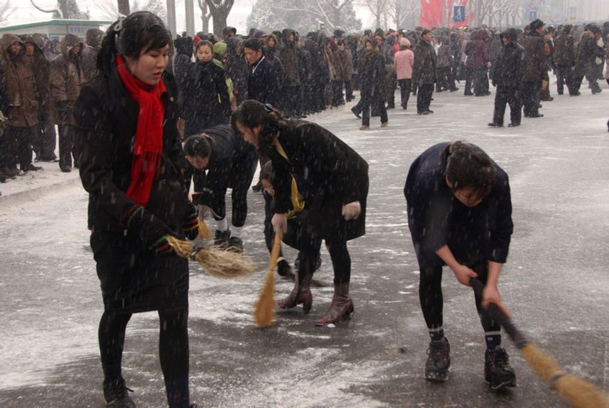 Pyongyang residents sweep snow from the streets before the funeral procession for late North Korean leader Kim Jong Il.  (AP Photo)