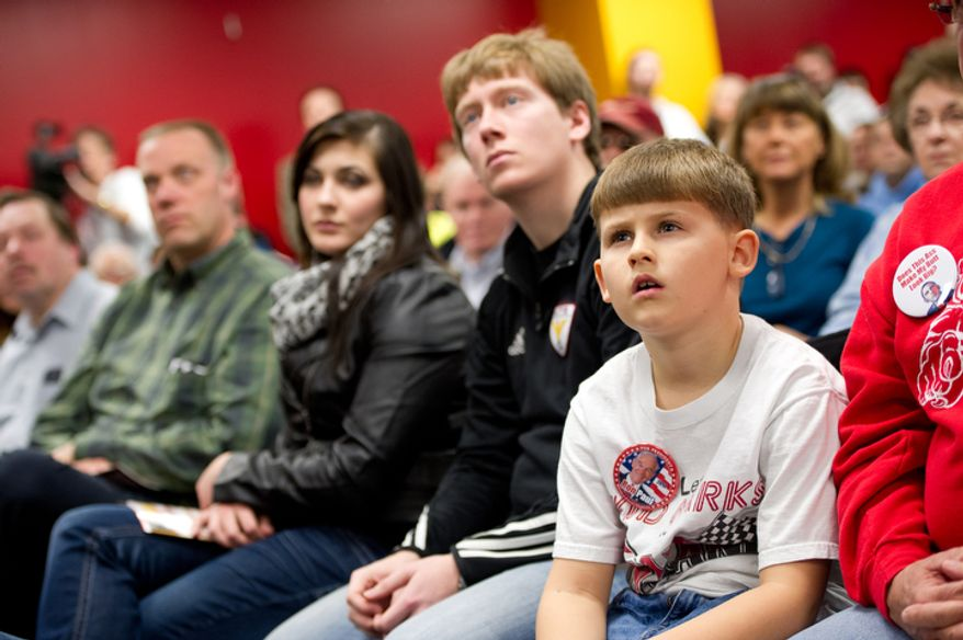 8 year old Mike Baker of Newton, Iowa listens as Republican presidential candidate Ron Paul delivers a speech at a Jasper County town hall meeting held at the inner track of the Iowa Speedway, Newton, IA, Wednesday, December 28, 2011. (Andrew Harnik / The Washington Times)