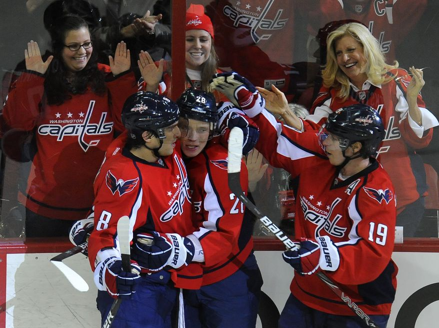 Washington Capitals' Alexander Semin, center, is congratulated by teammates Alex Ovechkin (8) and Nicklas Backstrom (19) after he scored his second goal of the game against the New York Rangers during third period of their hockey game, Wednesday, Dec. 28, 2011, in Washington. The Caps won, 4-1. (AP Photo/Richard Lipski)