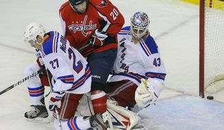 New York Rangers' goalie Martin Biron has his vision blocked by teammate Ryan McDonagh (27) as Washington Capitals' Troy Brouwer (20) slips the puck slip past him during second period of their NHL game, Wednesday, Dec. 28, 2011, in Washington. (AP Photo/Richard Lipski)