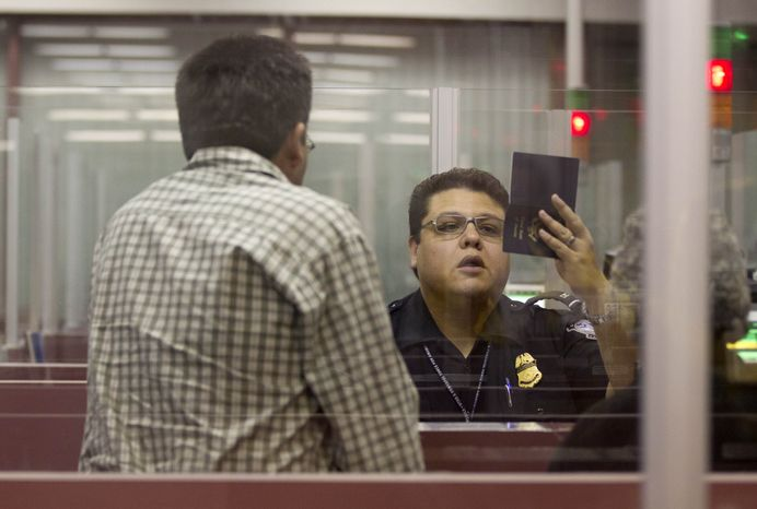 A U.S. Customs and Border Protection officer checks the passport of a foreign visitor at McCarran International Airport in Las Vegas on Tuesday, Dec. 13, 2011. (A