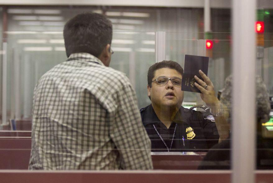 A U.S. Customs and Border Protection officer checks the passport of a foreign visitor at McCarran International Airport in Las Vegas on Tuesday, Dec. 13, 2011. (AP Photo/Julie Jacobson)