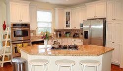 The kitchen has white solid-wood cabinets, stainless steel appliances and a granite-topped island.