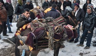 People mount bodies onto mules after Turkey's air force attacked suspected Kurdish rebels on Wednesday night, killing 35, many of them believed to be smugglers mistaken for guerrillas. It was one of the largest one-day civilian death tolls incurred during Turkey's 27-year drive against militant Kurds seeking autonomy. (Associated Press)