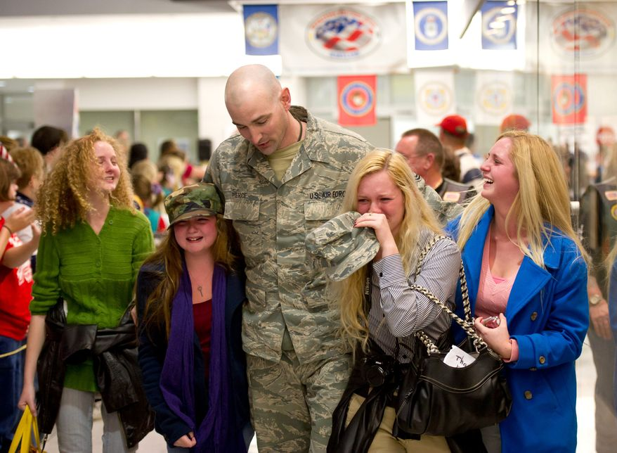 Air Force Tech Sgt. Matthew Pierce is swarmed by daughters (from left) Kimi, 16; Kathleen, 11; Keri Lu, 14, and Kris, 18, as he returns home Dec. 16 from a six-month stint in Afghanistan, one of his numerous deployments to both Iraq and Afghanistan in his 11 years in the military.