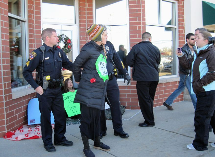 Megan Felt, 24, is arrested during an Occupy the Caucuses protest outside Rep. Ron Paul's Iowa campaign headquarters outside Des Moines on Thursday. Four others from the group of 15 were arrested. They dislike Mr. Paul's intent to dismantle the Environmental Protection Agency if elected president. (Des Moines Register via Associated Press)