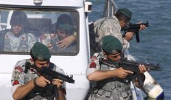 Iranian navy members take positions Dec. 28, 2011, during a drill in the Sea of Oman. (Associated Press)