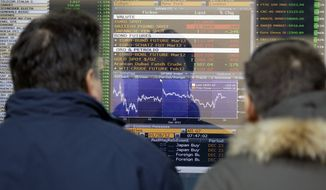 Two men check a monitor displaying the stock exchange index in Milan, Italy, Wednesday, Dec. 28, 2011. (AP Photo/Luca Bruno)