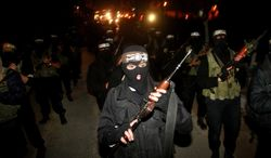 Masked Hamas militants march with their guns Dec. 27, 2011, during a parade in Gaza City to mark the third anniversary of the Israeli offensive on Gaza in 2008. (Associated Press)
