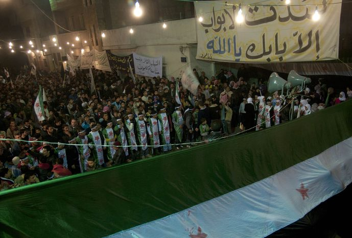 **FILE** Anti-Syrian regime protesters, some wearing Syrian revolution flags, gather Dec. 21, 2011, during a night demonstration in the Baba Amr area, in Homs province, Syria. (Associated Press)