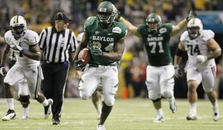 Baylor's Terrance Ganaway (center) rushes for a touchdown during the second half of Baylor's 67-56 victory over Washington in the Alamo Bowl at the Alamodome in San Antonio on Dec. 29, 2011. (Associated Press)