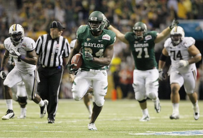 Baylor's Terrance Ganaway (center) rushes for a touchdown during the second half of Baylor's 67-56 victory over Washington in the Alamo Bowl at the Alamodome in San Antonio o