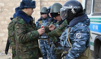 **FILE** A Kazakh riot police officer (left) instructs others Dec. 17, 2011, before their patrol in center of Zhanaozen, Kazakhstan. (Associated Press)