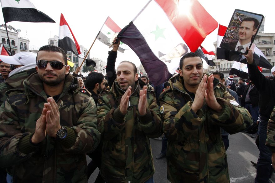 Syrian soldiers chant slogans Dec. 30, 2011, during a pro-regime rally in Damascus, Syria. The rebel Free Syrian Army said it has stopped its offensive against government targets during a month-long mission by Arab League monitors, saying it wants to expose how the regime is killing peaceful protesters. (Associated Press)