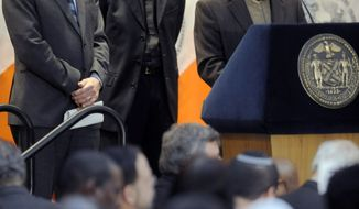 Imam Mohammed Sherzad (right) gives an invocation while Dr. Anthony Marx (left), president and CEO of the New York Public Library, and Father Joseph McShane of Fordham University, listen Dec. 30, 2011, during the mayor's annual interfaith breakfast at the New York Public Library in New York. (Associated Press)