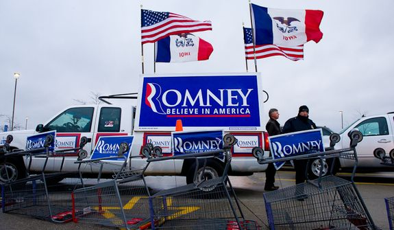 Campaign posters for Republican presidential candidate Mitt Romney can be seen in the parking lot where a cold, rainy, early morning rally is held at a Hy-Vee grocery store, West Des Moines, IA, Friday, December 30, 2011. (Andrew Harnik / The Washington Times)