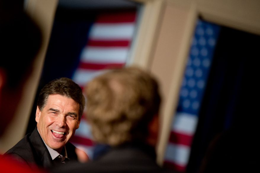 Republican presidential candidate Rick Perry laughs before being welcomed to the podium to speak at a fundraiser held at the Mason City Country Club, Mason City, IA, Friday, December 30, 2011. (Andrew Harnik / The Washington Times)